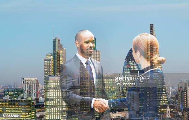 Two people shaking hands with London buildings