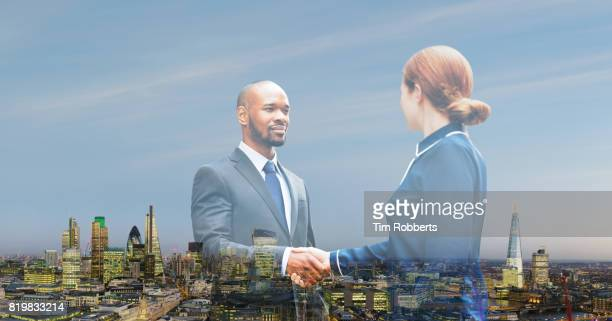 Two people shaking hands with London skyline