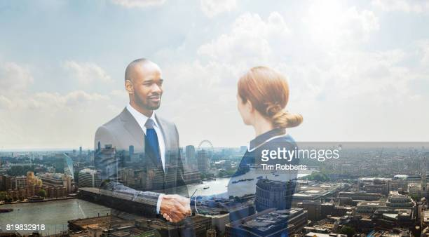 Two people shaking hands with London view
