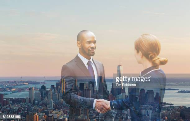 Two people shaking hands with New York view