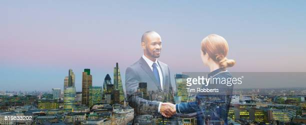 Two people shaking hands with view of London
