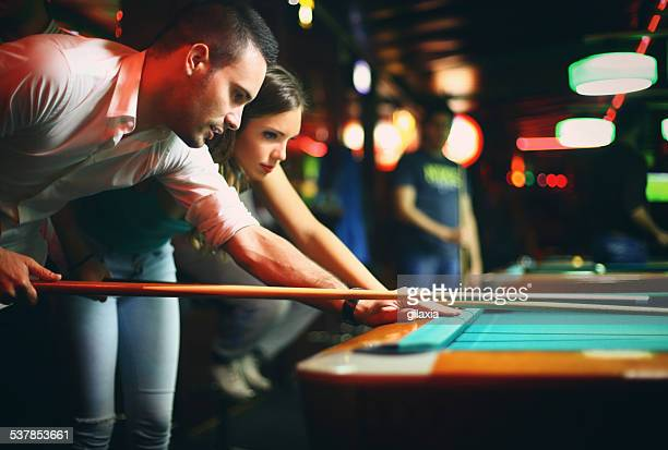 Two people shooting pool on weekend night.