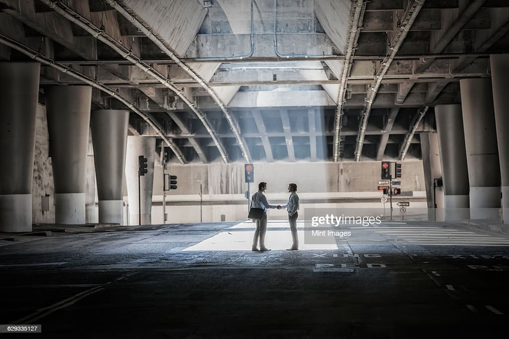 Two people silhouetted in a patch of light in a city underpass.