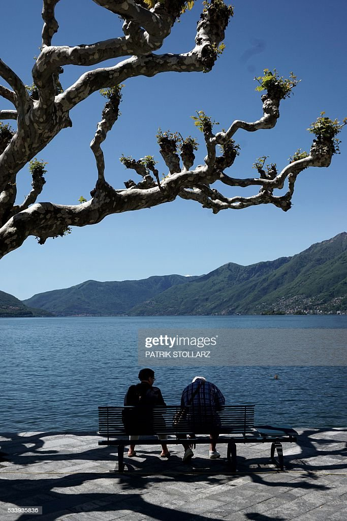 Two people sit on a bench looking out at Lago Maggiore also called Lake Langen in the town of Ascona on May 24, 2016. The German national football team will train here from May 24 until June 3, 2016 for the EURO 2016 taking place in France. / AFP / PATRIK