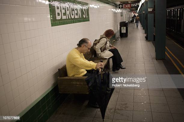 Two people sit on a bench waiting for the subway to arrive November 4 2010 in Brooklyn New York New York's Metropolitan Transit Authority recently...