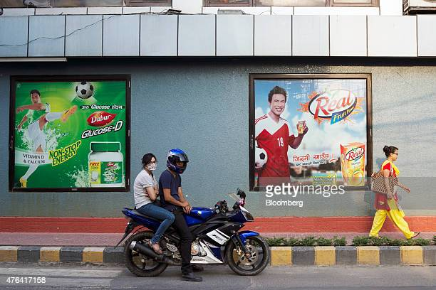 Two people sit on a motorcycle in front of advertisements displayed on a wall outside a supermarket in Kathmandu Nepal on Saturday May 30 2015...