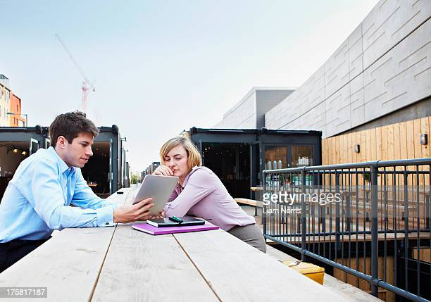 Two people sitting at table using digital tablet outdoors