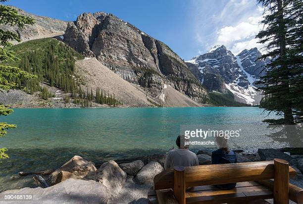 Two people sitting by Moraine Lake, Banff National Park, Canadian Rockies, Alberta, Canada