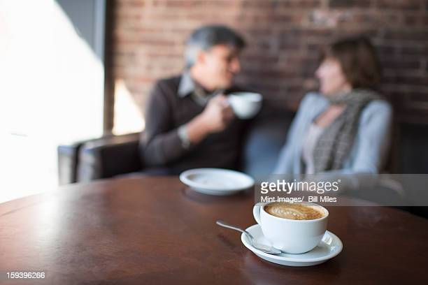 Two people sitting in a coffee shop. A man holding a white china of and drinking. Sitting beside a woman. A table with a large full cup of  cappuccino coffee.