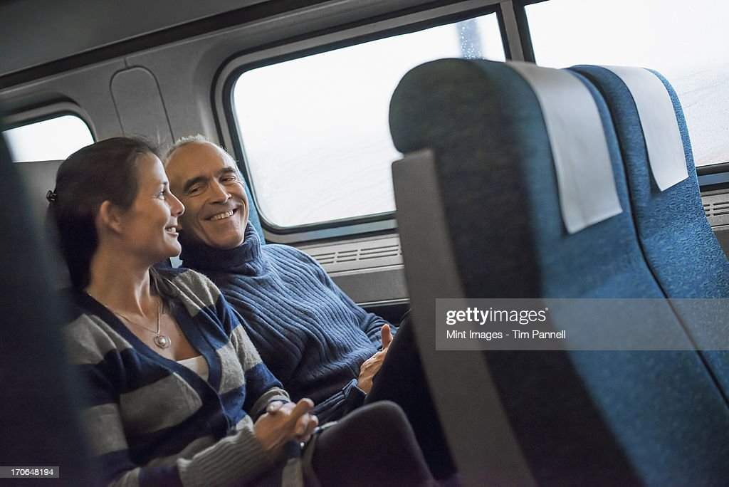 Two people sitting in a railway carriage, smiling. Taking a train journey. : Stock Photo