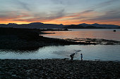 Two people skimming stones across the water at Easdale island as the sun is setting over the neighbouring inner Hebridean island of Mull on...