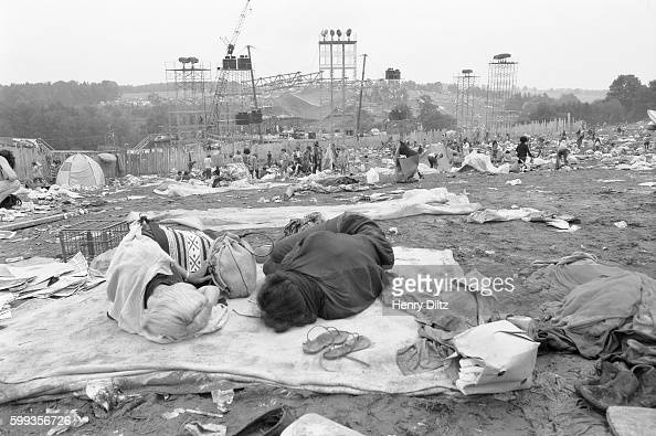 Two people sleep among piles of debris at the end of the free Woodstock Music and Art Fair The festival took place on Max Yasgur's dairy farm which...