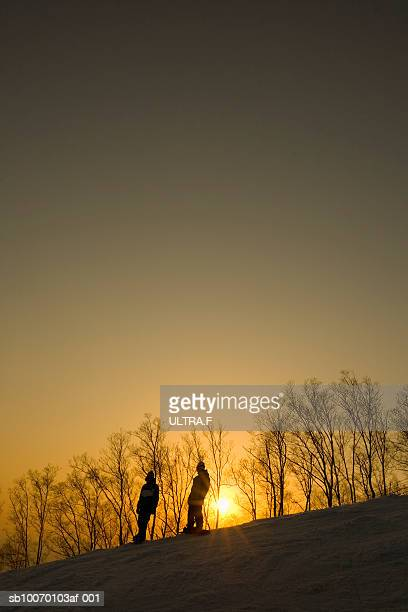 Two people snowboarding at sunset