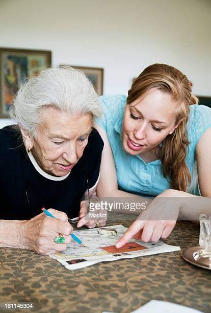 Two people solving crosswords