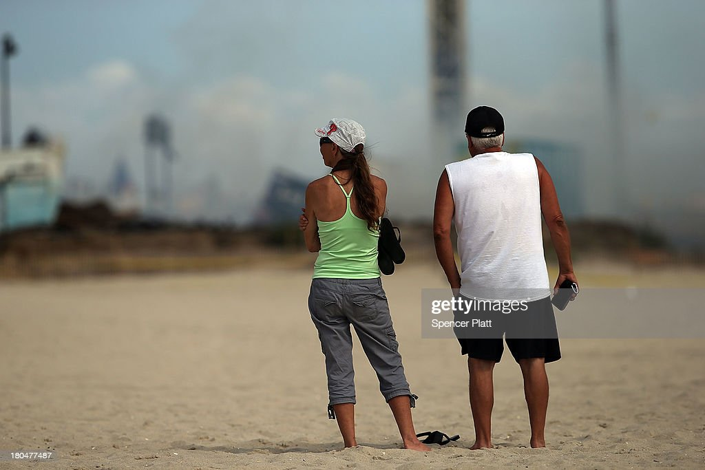 Two people stand near the scene of a massive fire that destroyed dozens of businesses along an iconic Jersey shore boardwalk on September 13, 2013 in Seaside Heights, New Jersey. The 6-alarm fire began in a frozen custard stand on the recently rebuilt boardwalk around 2:00 p.m. on September 12, and quickly spread in high winds. While there were no injuries reported, many businesses that had only recently re-opened after Hurricane Sandy, were destroyed in the blaze.