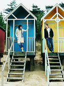 Two People Standing Full Length on the Steps of Their Beach Houses