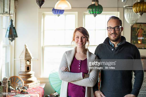 Two people standing in a store full of antique objects, a couple running a business.