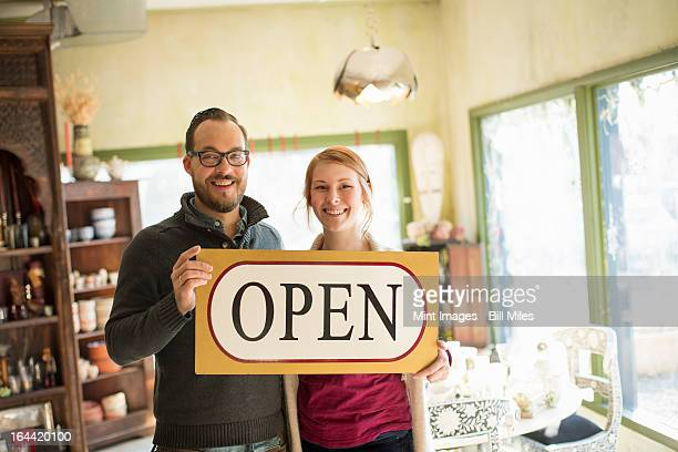 Two people standing in a store full of antique objects, a couple running a business. Holding a large sign saying OPEN.