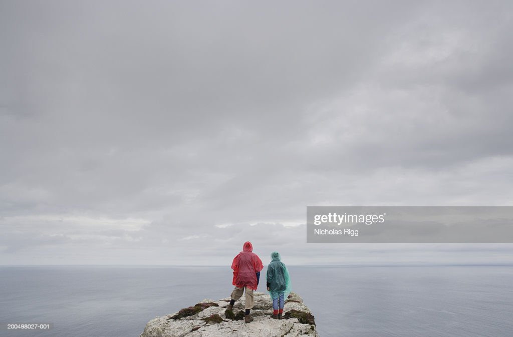 Two people standing on cliff near ocean, rear view : Stock Photo