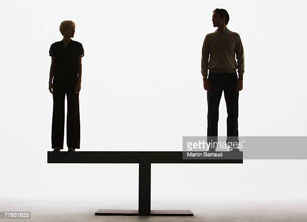 Two people standing on top of a plank