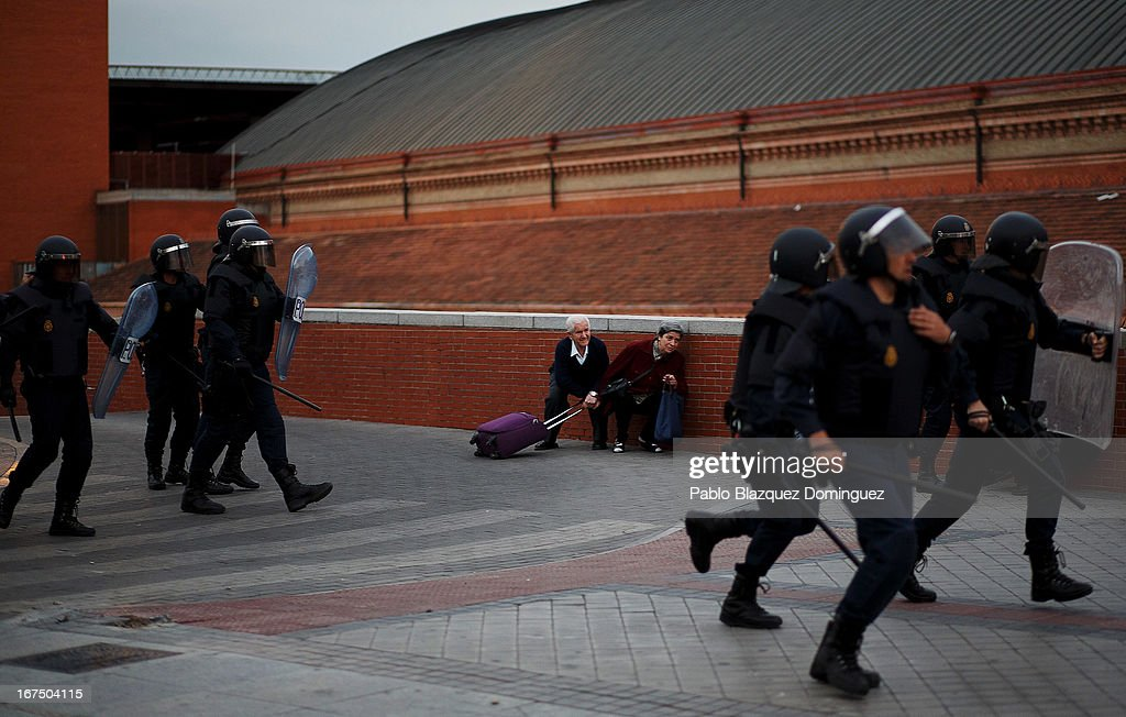 Two people take cover during clashes between riot police and demonstrators outside Atocha Station on April 25, 2013 in Madrid, Spain. Demonstrators marched from three locations in central Madrid in an attempt to converge on parliament, demanding a constitutional reform and protesting against financial measures introduced by Spanish Prime Minister Mariano Rajoy.