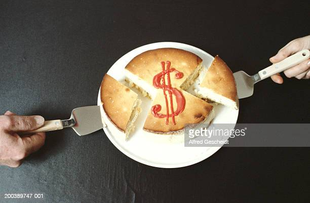 Two people taking slices from cake with dollar sign