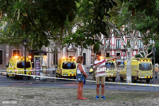 Two people talk near to the scene of a terrorist attack in the Las Ramblas area on August 17 2017 in Barcelona Spain Officials say 13 people are...