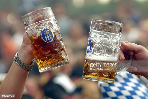 Two people toast with one liter mugs of beer at the Hofbraeuhaus tent on the opening day of the 2004 Oktoberfest September 18 2004 in Munich Germany...