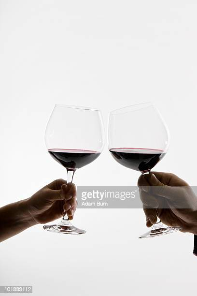 Two people toasting wineglasses, focus on hands