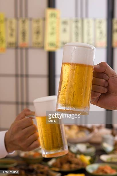 Two People Toasting with Beer at Izakaya