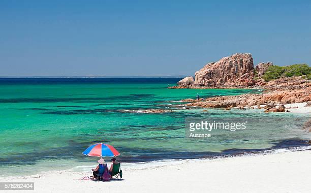 Two people under a beach umbrella and Castle Rock Dunsborough Western Australia Australia