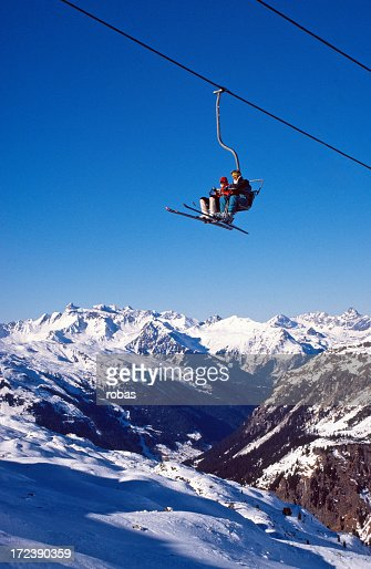 Two people using a ski lift to cross to the other side safe