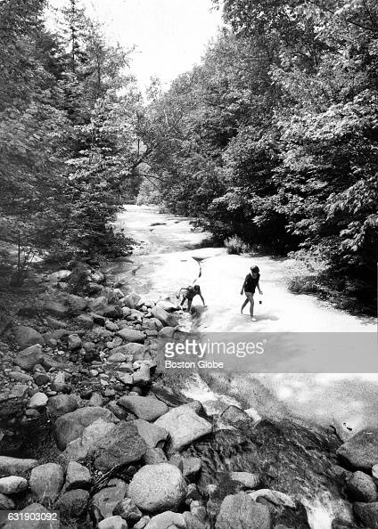 Two people wade in the water at the Flume Gorge a natural gorge extending 800 feet at the base of Mount Liberty in Franconia Notch State Park in...