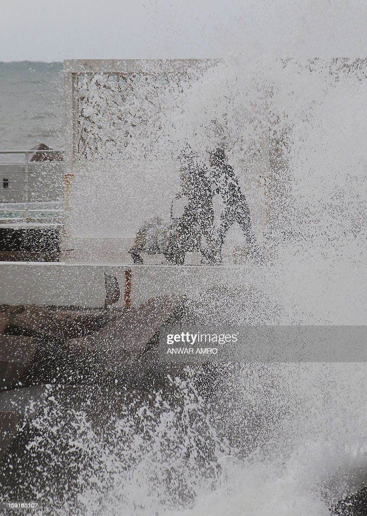 Two people walk along the promenade in Beirut as waves crash against the rocks in stormy weather conditions on January 9, 2013. A met office official at Beirut airport said the storm would continue and that lower temperatures would result in snowfall in the mountains as low as 300 metres (1,000 feet). AFP PHOTO/ANWAR AMRO