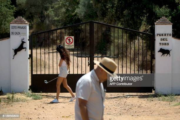 Two people walk in front of the entrance gate of 'Puerto del Toro' estate where the former head of Spanish bank Caja Madrid Miguel Blesa was found...
