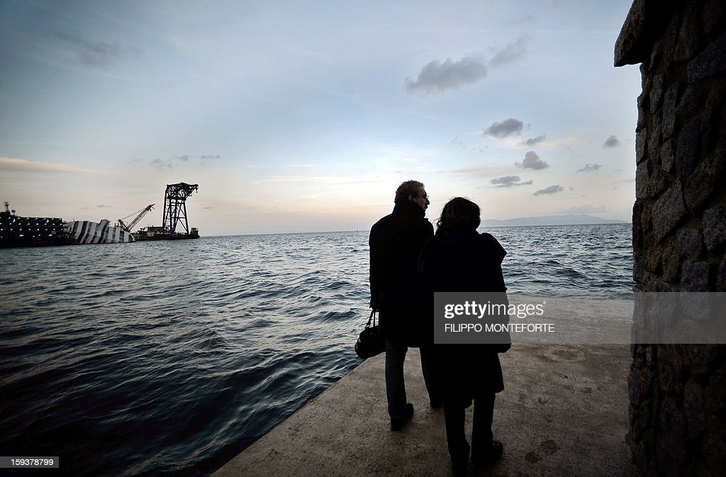 Two people walk in the port of the Italian island of Giglio on January 12, 2013. The Costa Concordia cruise ship (background at left) wreck will be removed from the island of Giglio by September at the latest, the head of Italy's civil protection agency said today, the eve of the first anniversary of the disaster which claimed 32 lives.