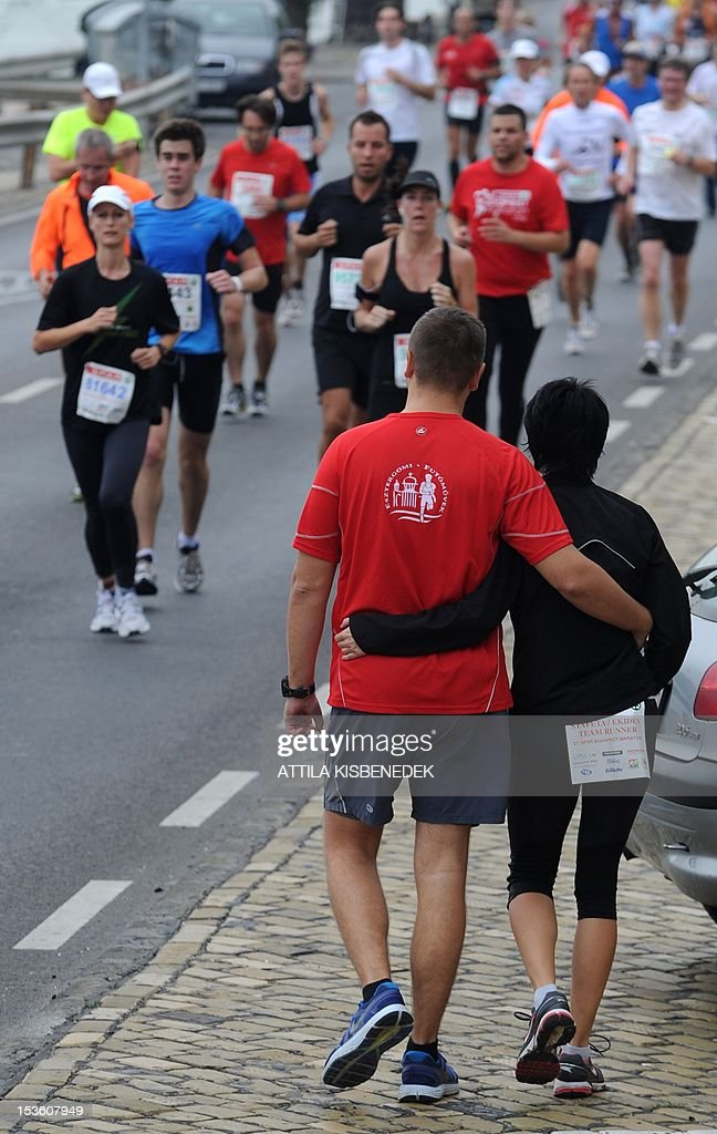 Two people walk next to participants of the 27 annual SPAR Budapest Marathon as they run next to the Danube River in Budapest, Hungary on October 7, 2012.