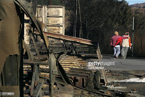 Two people walk past a line of nine burned truck trailers along a road near the burnedout former Egg City factory which neighbors say was converted...