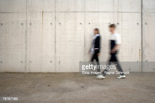 Two people walking past a wall