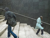 Two people walking up and down steps in rain, side view