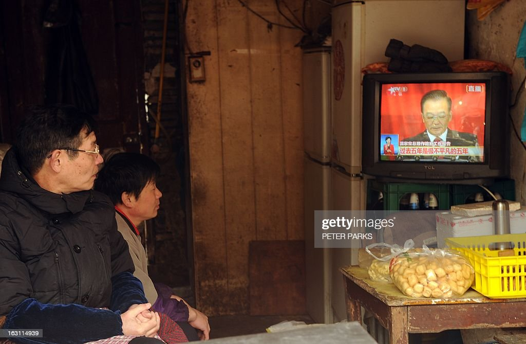Two people watch a television set showing Chinese Premier Wen Jiabao (R) speaking during the opening session of the National People's Congress (NPC), inside their small shop in Shanghai on March 5, 2013. Premier Wen targeted 2013 growth of 7.5 percent and vowed an unwavering fight against corruption as the world's second-largest economy opened its annual parliamentary session. AFP PHOTO/Peter PARKS