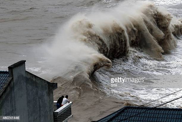 Two people watch huge waves from a balcony as typhoon Chanhom comes near Wenling east China's Zhejiang province on July 10 2015 Typhoon Chanhom...