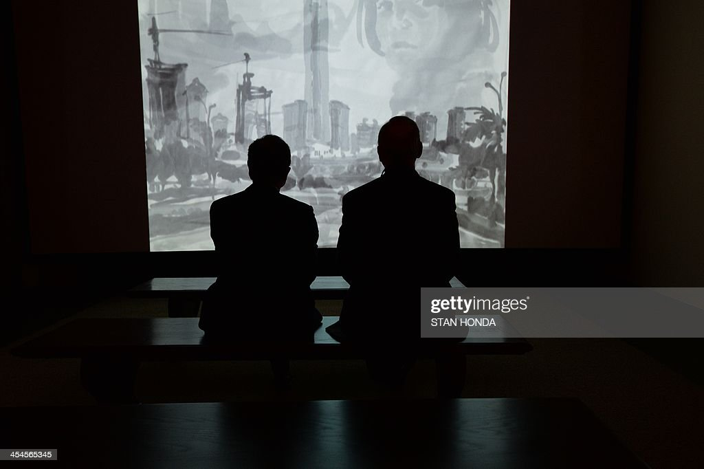 Two people watch the animated video 'Ink Diary' by Chen Shaoxiong at the exhibition 'Ink Art: Past as Present in Contemporary China' at the Metropolitan Museum of Art on December 9, 2013 in New York. A major exhibition of 70 pieces of art by 35 contemporary artists born in China goes on view to the public on December 11. AFP PHOTO/Stan HONDA ++RESTRICTED