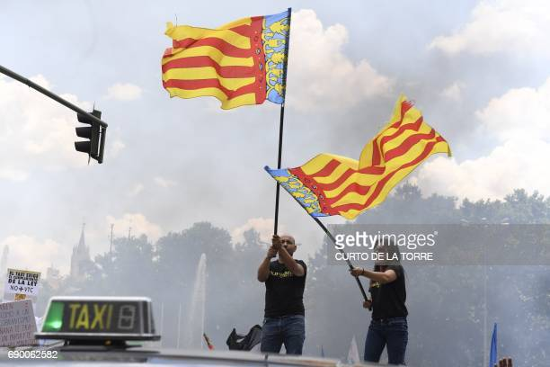 Two people wave flags during a taxi strike action held between Atocha Train station to Neptuno Square in Madrid on May 30 2017 against competition...