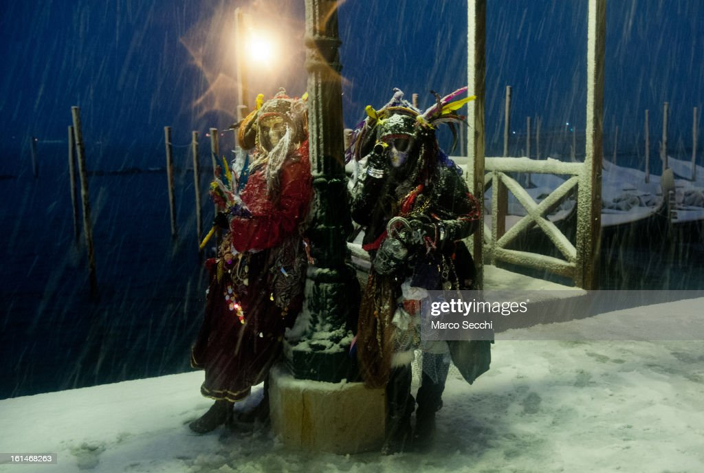 Two people wearing carnival costumes are seen in Saint Mark's Square during heavy snow on February 11, 2013 in Venice, Italy. Heavy snow, High water, wind and rain has been forecasted for today.