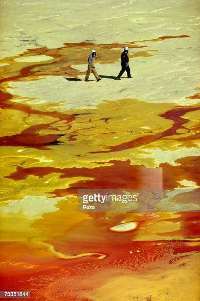 Two people wearing gas masks walk on a sulphur flat on an onsite plant at the Tengiz oil field where sulphur is separated from crude oil and gas on...