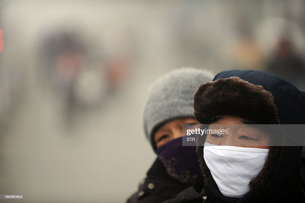 Two people wearing masks ride a bike in the heavy smog on a street of Haozhou, central China's Anhui province on January 30, 2013. Across China public frustration mounted this week as dense smog blanketed swathes of the country, with even state-run media questioning the authorities' ability to meet their goal of building a 'beautiful China'. CHINA