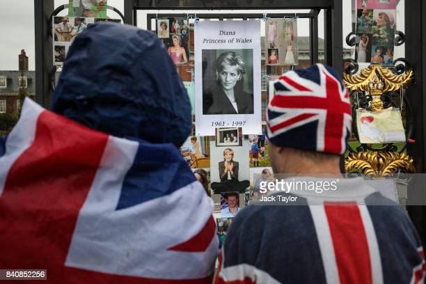 Two people wearing Union Jack outfits pause in front of floral tributes photographs and messages on an entrance gate to Kensington Palace ahead of...