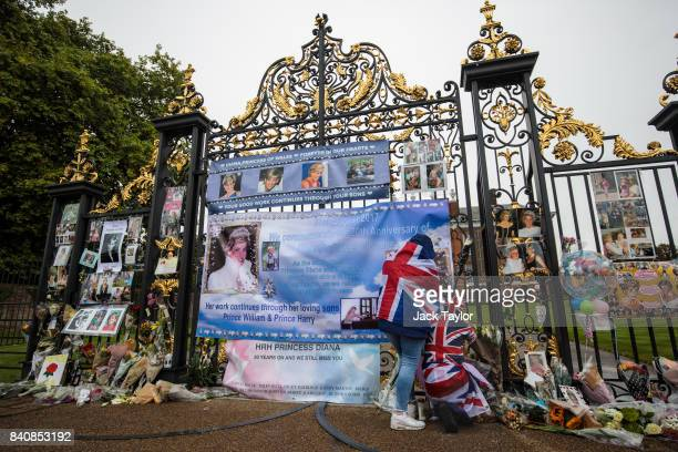 Two people wearing Union Jack outfits secure a banner among floral tributes and messages on an entrance gate to Kensington Palace ahead of the 20th...