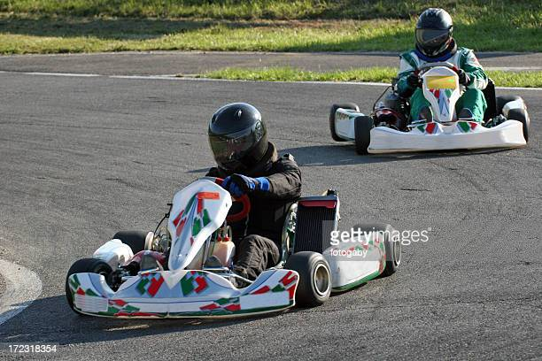 Two people with helmets racing go-carts around a track
